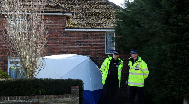 Police officers at the scene in Canterbury, Kent, after two people were found dead following a bust-up at the property