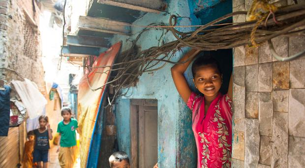 A girl looks out of a doorway in the Ambedkar Nagar slum area in Mumbai