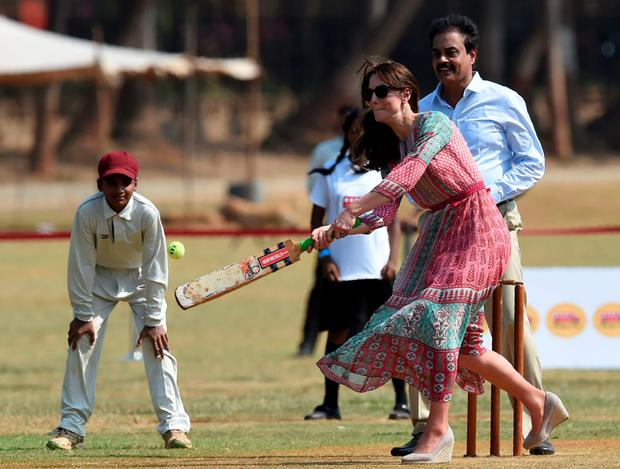 The Duchess of Cambridge, watched by former Indian cricketer Dilip Vengsarkar, plays a game of cricket with children at The Oval Maidan in Mumbai