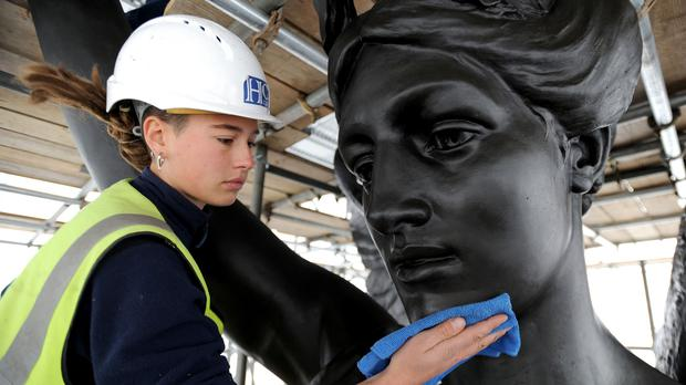 Freelance sculpture conservator Scarlett Hutchin, working for English Heritage, buffs wax polish applied to artist Adrian Jones' sculpture Quadriga, on top of Wellington Arch at Hyde Park Corner