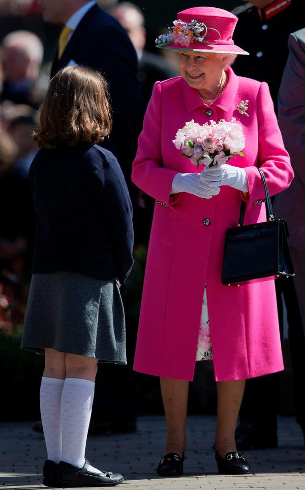 The Queen is given a bouquet of flowers by a schoolgirl yesterday