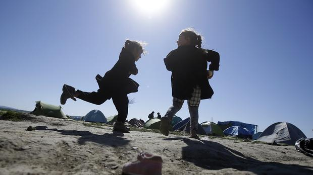 Children play in a makeshift camp at the northern Greek border point of Idomeni (AP)