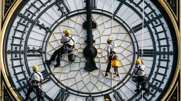 Workmen cleaning one of the clock faces of the Elizabeth Tower which houses Big Ben