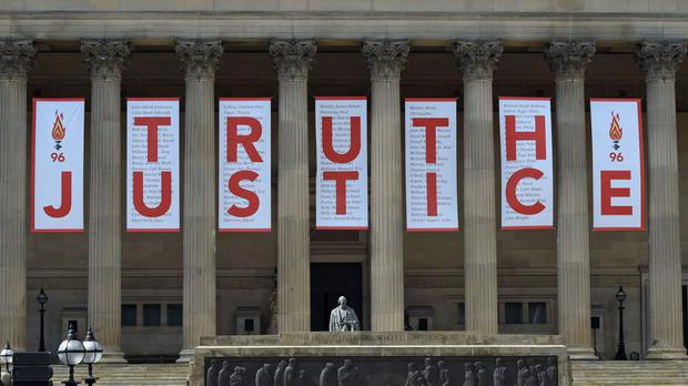 A banner is unveiled at St George's Hall in Liverpool after the inquest jury ruled the 96 victims in the Hillsborough disaster had been unlawfully killed