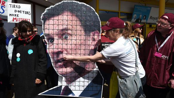 A member of the CWU pins a pin to a cardboard cut-out of Health Secretary Jeremy Hunt as members of the union join junior doctors on the picket line outside of the Royal Bournemouth Hospital in Bournemouth