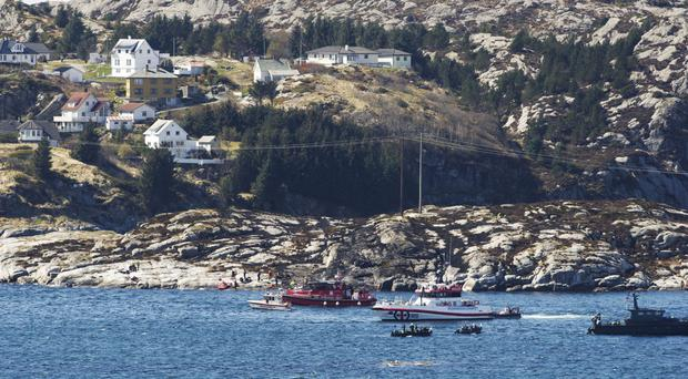 A search and rescue vessel patrols off the island of Turoey, near Bergen, Norway, as emergency workers on the shoreline attend the scene after a helicopter crash (AP)