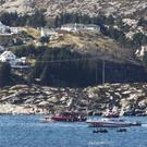 A search and rescue vessel patrols off the island of Turoey, near Bergen, Norway, as emergency workers on the shoreline attend the scene after a helicopter crashed believed to be have 13 people aboard, Friday April 29, 2016. The helicopter carrying around 13 people from an offshore oil field crashed Friday near the western Norwegian city of Bergen, police said. Many are feared dead. (Marit Hommedal / NTB scanpix via AP) NORWAY OUT