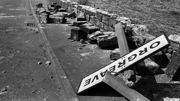 A twisted sign, felled concrete posts and a broken wall tell the story of violence outside a coking plant in Orgreave, South Yorkshire.