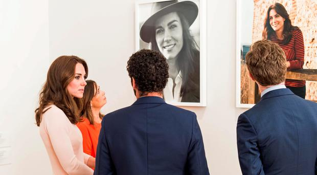 The Duchess of Cambridge views the two portraits of herself displayed in the National Portrait Gallery on a visit to the Vogue 100: A Century of Style exhibition in central London yesterday