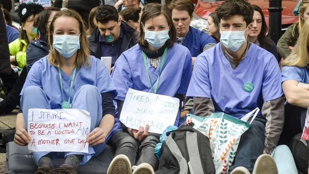 Junior doctors in scrubs and masks sit down in a silent protest outside Bristol Royal Infirmary on the second day of their all-out strike