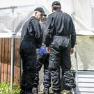 Police enter the tarpaulin-covered garden at the former home of paedophile couple David and Pauline Williams