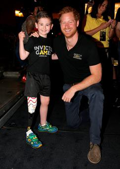 Prince Harry meets seven-year-old amputee Rio Woolf during the Invictus Games in Florida