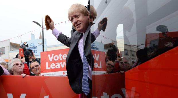 Former Mayor of London Boris Johnson brandishes a Cornish pasty as he boards the Vote Leave campaign bus in Truro, Cornwall