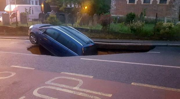 A car which has partially disappeared down a sinkhole in Woodland Terrace in Greenwich, south-east London (Metropolitan Police/Twitter/PA)