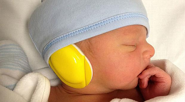 A baby with ear muffs before having an MRI scan (Imperial College London/PA)