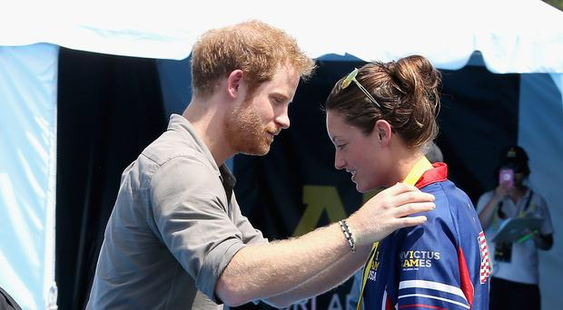 Prince Harry presenting Elizabeth Marks with a gold medal