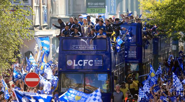 Leicester City's team celebrate on the bus as fans look on during the open top bus parade through the city centre
