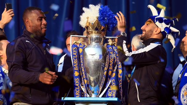 Wes Morgan (left) and Riyad Mahrez place a wig on the trophy on stage at Victoria Park after the open top bus parade through Leicester