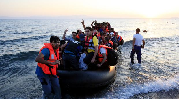 Migrants and refugees in a rubber dinghy arriving on the beach at Psalidi near Kos Town, Kos.