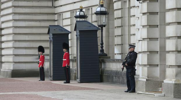 An armed police officer and soldiers from the Irish Guards in the forecourt of Buckingham Palace