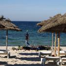 An armed policeman on the beach in Sousse following the terrorist attack, as the Foreign Office has been urged to relax its advice, warning against all but essential travel to the North African country