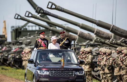 The Queen drives past guns used by the Royal Regiment of Artillery