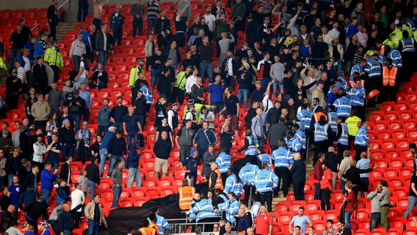 Police and stewards with fans in the stands at Wembley