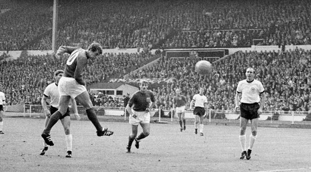 England's Geoff Hurst heads the equalising goal, watched by team mate Roger Hunt, centre, and West Germany's Wolfgang Weber, left, and Willi Schulz, right