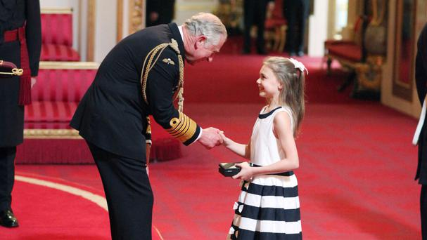Gabriella Rummery, 10, from Kent, picks up a CBE (Commander of the Order of the British Empire) medal on behalf of her late grandmother Jill Tookey