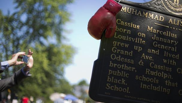 Boxing gloves hang on a historical marker outside the childhood home of Muhammad Ali in Louisville (AP)