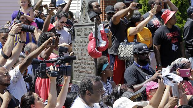 Boxing gloves hang on the historic site plaque in front of Muhammad Ali's boyhood home as people watch his funeral procession (AP)