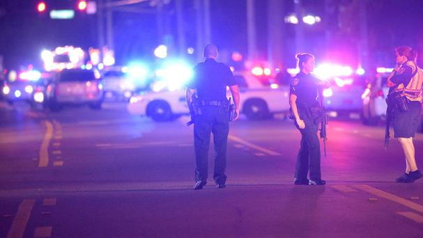 Police officers stand guard in the street at the scene of the shooting at a nightclub in Orlando (AP)