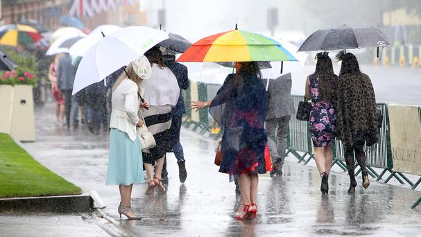 Racegoers arrive in the rain at Royal Ascot