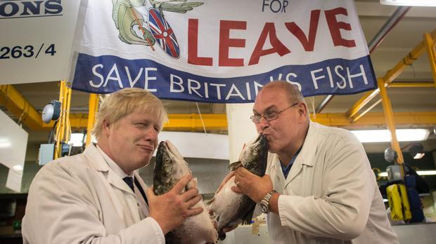 Boris Johnson, left, kisses a wild salmon as he is shown around Billingsgate Fish Market in London with porter Greg Essex, uncle of TV presenter Joey Essex