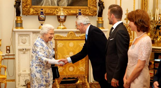 Queen Elizabeth II greets former Prime Minister Sir John Major and David Beckham as they attend the Queen's Young Leaders Awards at Buckingham Palace