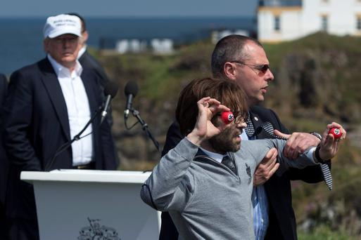 Lee Nelson is led away as he attempts to present Donald Trump with a set of swastika-branded golf balls at Trump Turnberry resort yesterday