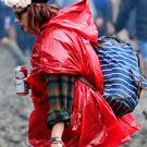 A festivalgoer in the mud at the Glastonbury Festival, at Worthy Farm in Somerset.