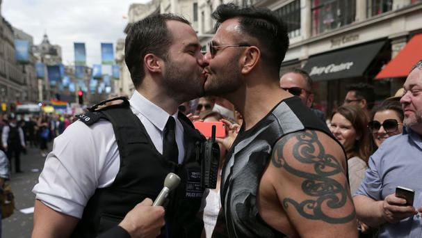 A policeman kisses his boyfriend after proposing to him during the Pride in London parade