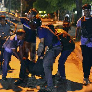 People help an injured person after a group of gunmen attacked a restaurant popular with foreigners in a diplomatic zone of the Bangladeshi capital Dhaka (AP)