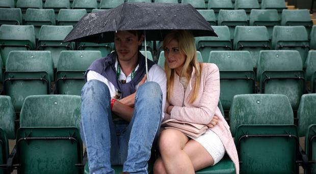 A couple shelter from the rain on court one