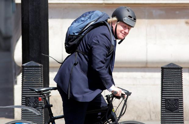 Boris Johnson rides his bicycle through the Westminster area yesterday