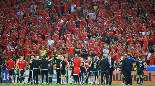 Wales fans cheer the players and staff following the Euro 2016, semi-final defeat in Lyon
