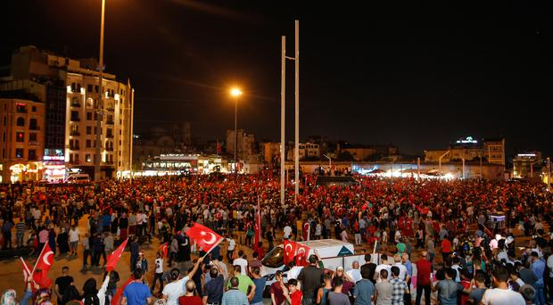 People gather at a pro-government rally in Istanbul's Taksim Square (AP)