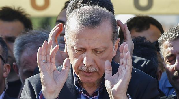 Turkish president Recep Tayyip Erdogan prays at the funeral of his campaign manager Erol Olcak, who was killed along with his 16-year old son at the Bosphorus Bridge (AP)