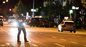 A masked policeman stands on the street in front of the Olympia mall where the massacre took place (AP)