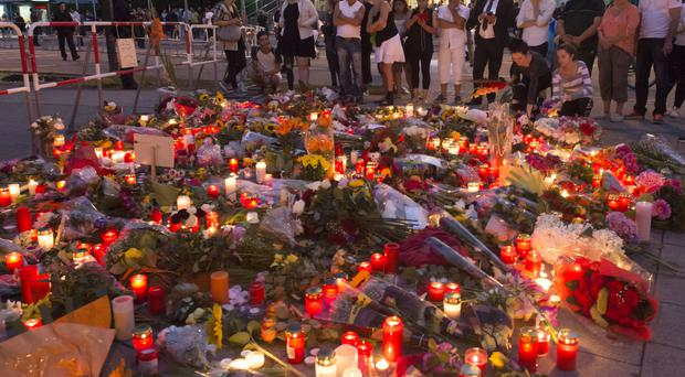 Flowers and candles left at the Olympia shopping centre in tribute to the nine people shot dead by a teenage gunman