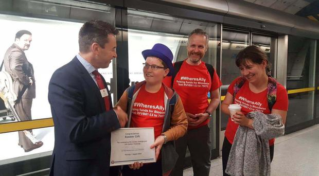 Alasdair Clift, 13, accompanied by his mother Caroline and father Richard, is presented with a certificate by Mark Wild, managing director of London Underground at Southwark Underground station