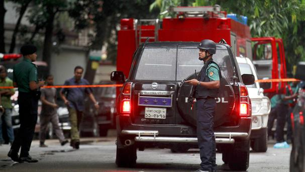 Bangladeshi security officers cordon off an area after militants attacked a restaurant in Dhaka (AP)