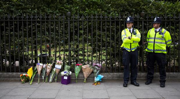 Police officers stand guard by flowers left in Russell Square where Darlene Horton was stabbed to death