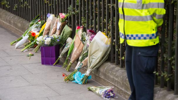 Floral tributes resting against railings near the scene of the fatal stabbing in Russell Square
